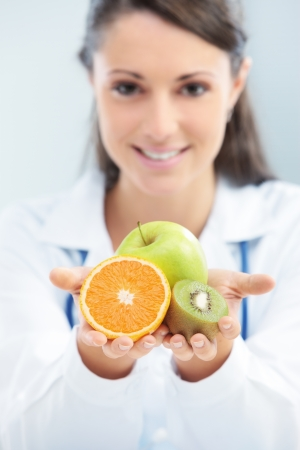 Nutritionist Doctor holding some fruits in her hand photo