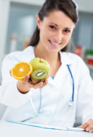 dietology: Nutritionist Doctor holding some fruits in her hand