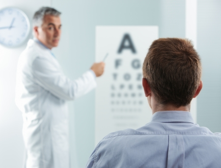 eye doctor: Optometrist and patient, doctor pointing at eye chart