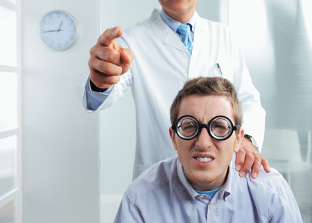 Optometrist pointing at eye chart, a nerd patient having difficulty photo