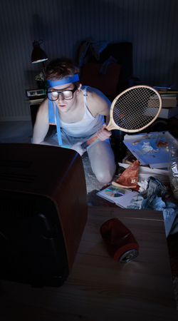 Young man tennis fanatic getting really into the tennis game on television Stock Photo - 22640225