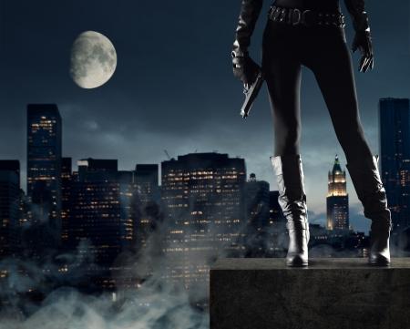 Sexy Vrouwelijke dief met pistool, new york op achtergrond Stockfoto