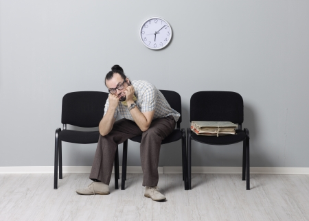 Depressed Man sitting alone in a waiting room for an appointment photo