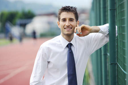 Portrait of young business man at sport field