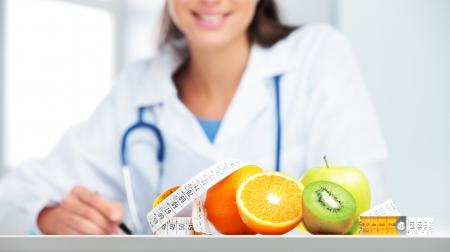그녀의 사무실에서 영양사 여성 의사입니다. 과일에 초점을 맞춘다.