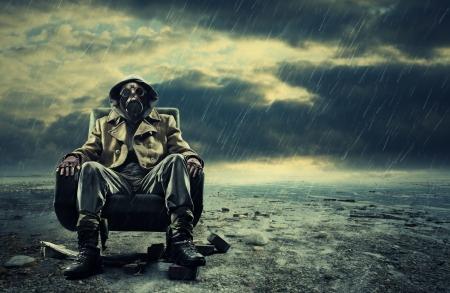 gasmasker: Een eenzame held die gasmasker draagt zittend op een stoel Stockfoto