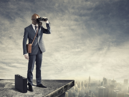 Businessman with gas mask looking through binoculars with a polluted city  photo