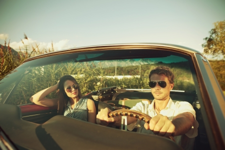 Couple taking a road trip in vintage convertible photo