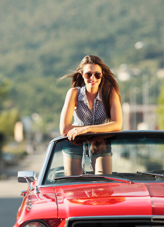 Beautiful young woman in a convertible car enjoying a summer day Stock Photo - 22849019