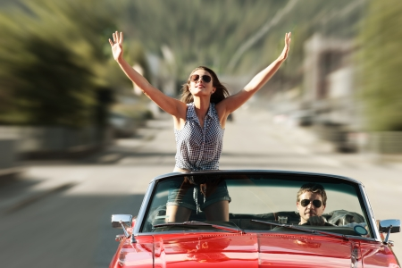 Happy young people in a convertible car Stock Photo - 22849030