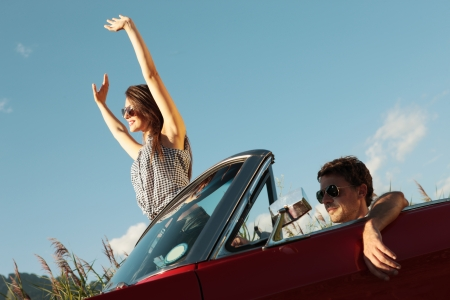 Happy young people in a convertible car photo