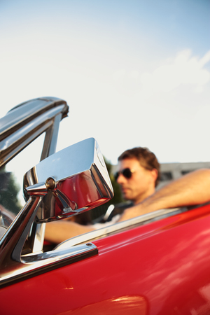 Handsome man driving a convertible car, focus on Rear-View Mirror Stock Photo - 22849026