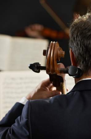 Symphony, cellist on foreground playing at the concert photo