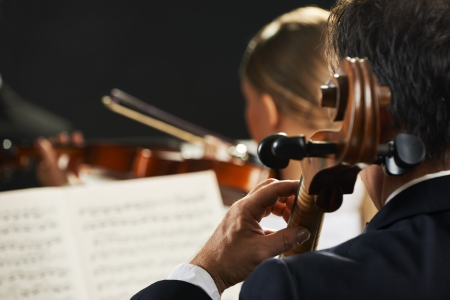 classical music: Symphony, cellist on foreground playing at the concert