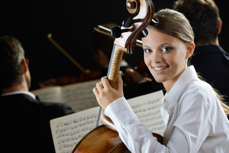 expressing positivity: Young beautiful woman playing cello in orchestra