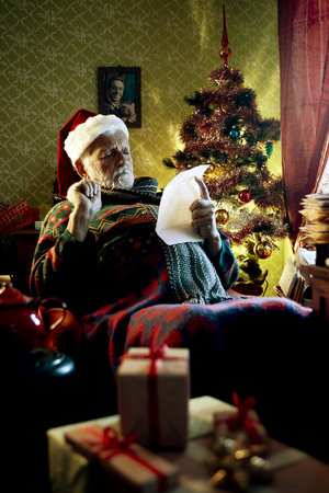 Portrait of Father Christmas sitting in armchair reading letters photo
