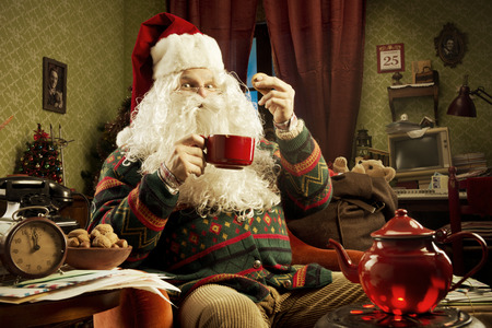 Portrait of Santa Claus sitting on armchair holding a cup of tea photo