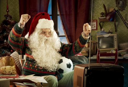 old fashioned christmas: Santa Claus watching a soccer match on tv