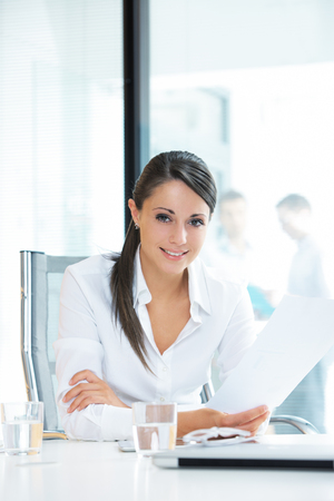 female office worker: Portrait of a pretty businesswoman smiling, blurred colleagues in the background