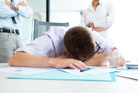 overwork: Young office worker is sleeping on the desk, executives behind him