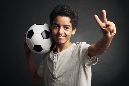 Portrait of young boy with a soccer ball signing victory