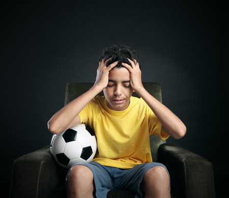 sad teen: Brazilian soccer fans sitting on armchair and watching sport on TV. Favorite team didnt win a match