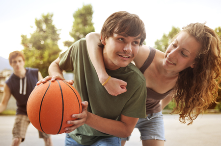 youth culture: Two boys and a girl playing a game of basketball on an outdoor court.