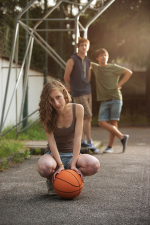 Teen Girl with basketball, her friends on the background photo
