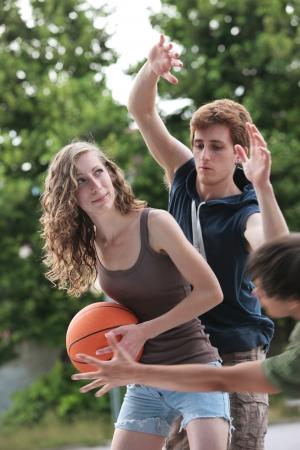 baloncesto chica: Dos niños y una niña jugando un partido de baloncesto en una cancha al aire libre. Foto de archivo