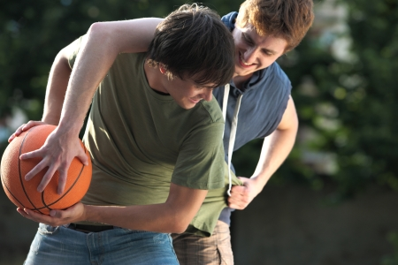 teenage guy: Boys playing a game of basketball on an outdoor court.