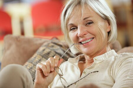 Portrait of a smiling senior woman sitting on couch photo