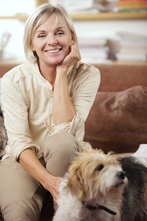 Portrait of a smiling senior woman sitting on couch with her dog photo