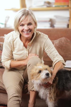 mujer con perro: Retrato de una mujer senior sonriente, sentado en el sofá con su perro Foto de archivo