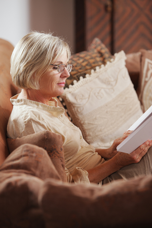 Mature Caucasian woman reading a book at home Stock Photo - 23159913