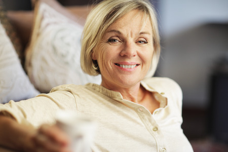 A smiling senior woman enjoying a cup of coffee  photo