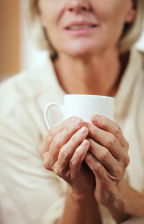 A pretty senior woman enjoying a cup of coffee, close up photo