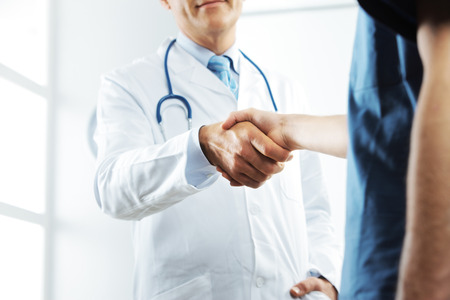 Two medical people handshaking at office  photo