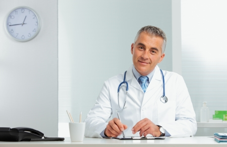 Mature male doctor sitting at desk in doctors room Stock Photo