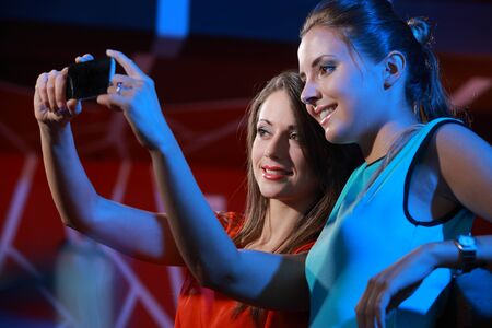 Two happy women at nightclub party taking a self-portrait with smartphone photo