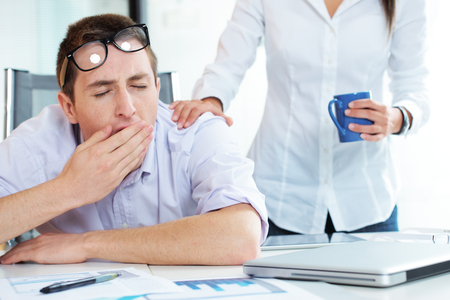 Young businessman is yawning, colleague gives him a cup of coffee photo