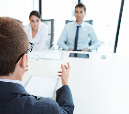 Two business people having job interview with young man photo