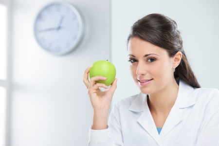 dietology: Nutritionist female Doctor holding a green apple