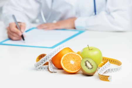 Nutritionist Doctor is writing a prescription. Focus on fruit photo