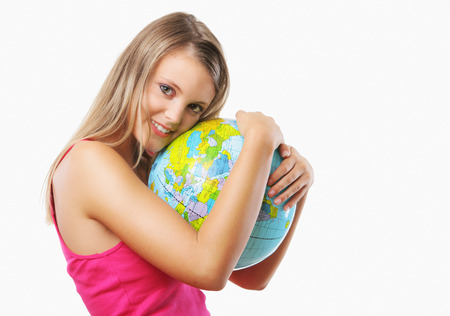 Portrait of a happy blonde girl embracing a globe against white background  photo