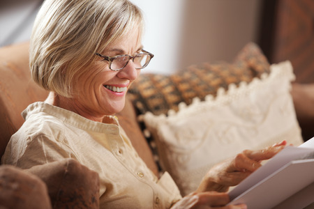 mature woman: Pretty mature woman passing her time by reading a book