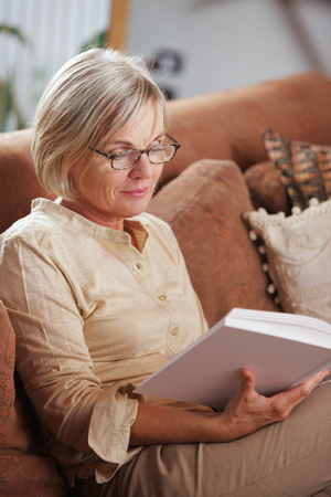 woman reading: Mature Caucasian woman reading a book at home