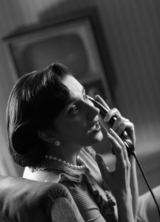 retro telephone: Woman talking on retro phone at home Stock Photo