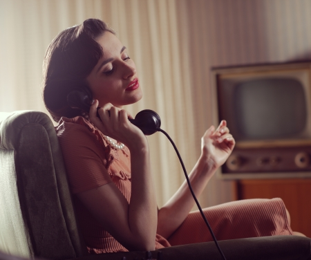 Vintage woman talking on retro phone at home photo