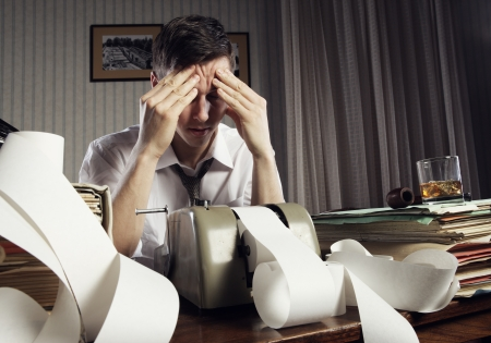 secretary desk: Tired businessman is sitting at a table full of paperwork