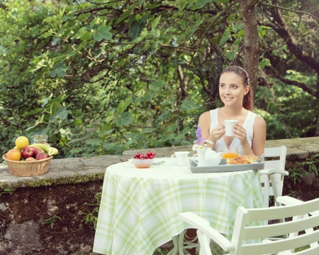 having breakfast: Young woman having breakfast in the garden on a summer day